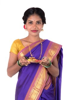 Indian woman performing worship, portrait of a beautiful young lady with pooja thali isolated on white wall