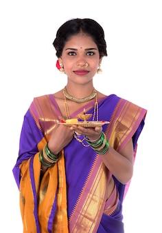 崇拝を行うインドの女性、白い背景で隔離のプージャーターリーと美しい若い女性の肖像画