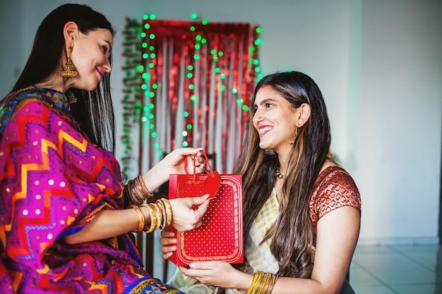 ディワリ祭で友人から贈り物を受け取るインドの女性