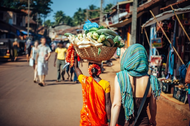 An indian woman in red sari carries a large basket of vegetables on her head. tourists and locals in india. a crowded street in gokarna, karnataka