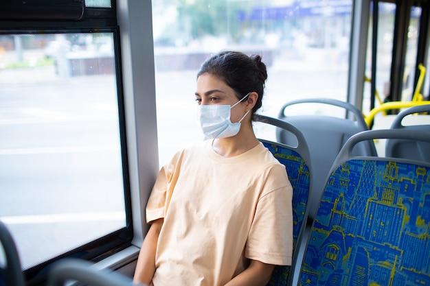 의료용 안면 마스크를 쓴 인도 여성이 대중교통 버스를 타고