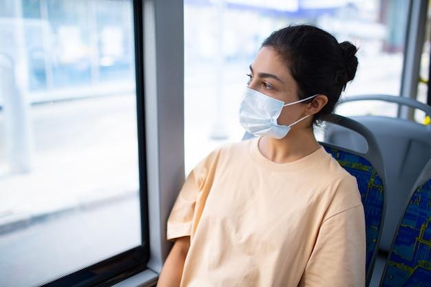Индийская женщина едет в автобусе общественного транспорта или трамвае в медицинской маске