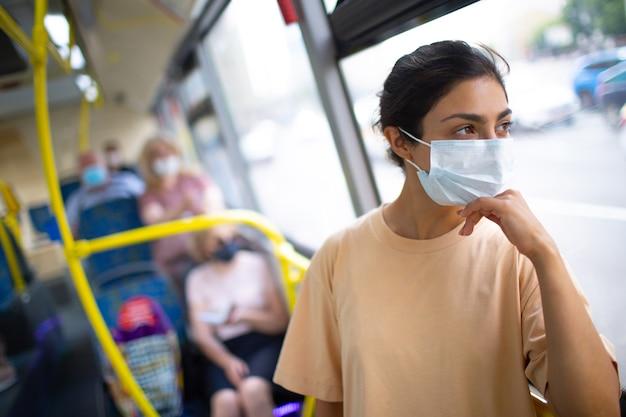 인도 여성은 의료용 안면 마스크를 쓰고 대중교통 버스나 트램을 타고