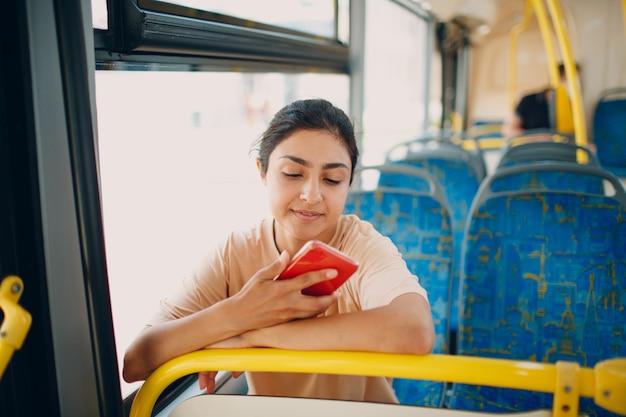 Индийская женщина едет в автобусе общественного транспорта с помощью мобильного телефона