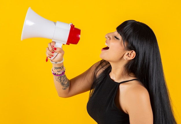 Indian woman screaming with a megaphone, yellow space