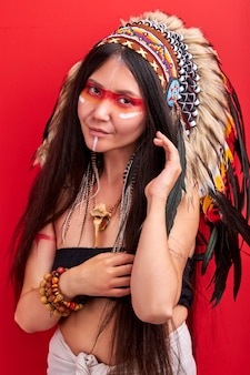 Indian woman in shamanic costume posing, having shy smile