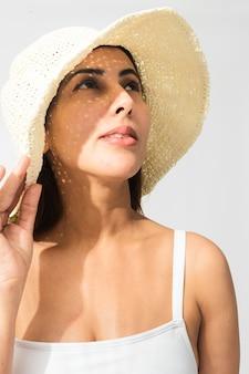 わらの日よけ帽をかぶったインドの女性