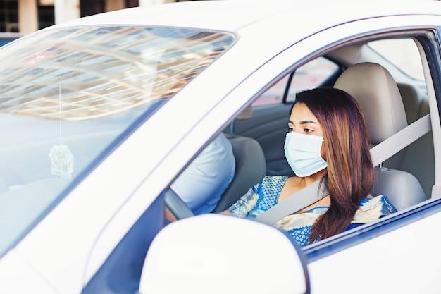 車の中でフェイスマスクを身に着けているインドの女性