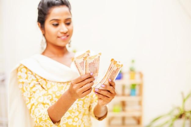 Индийская женщина в традиционной этнической одежде счастливо считает деньги