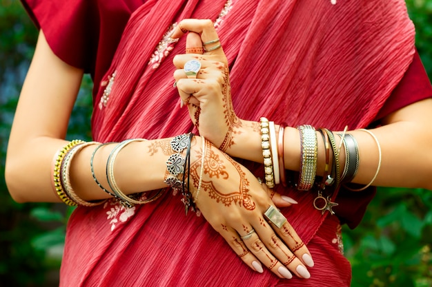 Indian woman with accessories: bracelets and rings wears red inidan paranja doing indian symbol yin yang by hands. colorized hands in mehndi style by brown henna. indian culture and style concept