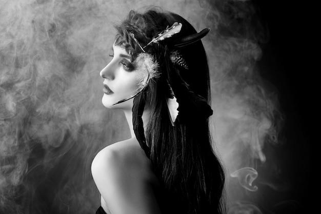 그녀의 머리에 깃털을 가진 인도 여자, 연기에 어두운 배경에 아메리칸 인디언 소녀 아름다움의 초상화. 깨끗한 피부, 대비 메이크업으로 아름다운 얼굴