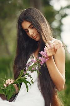 長い髪のインドの女性。青いドレスを着た女性。手つかずの自然を持つ少女。