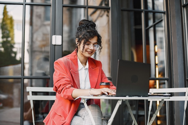 Indian woman working on a laptop in a street cafe. wearing stylish smart clothes -  jacket, glasses Free Photo