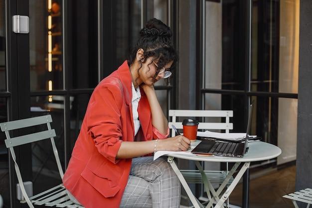 ストリートカフェでラップトップに取り組んでいるインドの女性。スタイリッシュでスマートな服を着る-ジャケット、メガネ