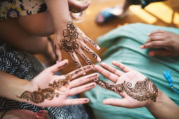 Indian women showing hand with henna tattoo art (mehndi)