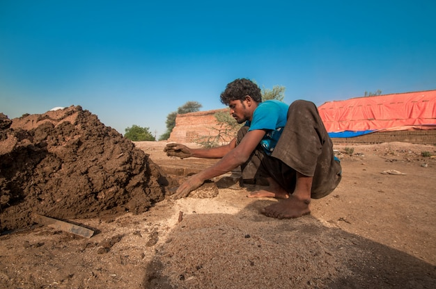 Indian workers making traditional bricks by hand in the brick factory