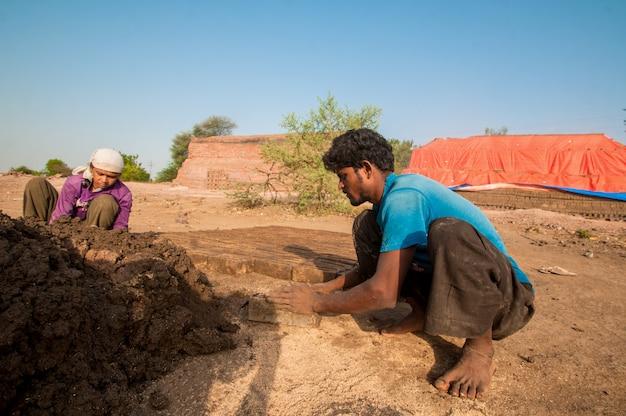 Индийские рабочие делают традиционные кирпичи вручную на кирпичном заводе