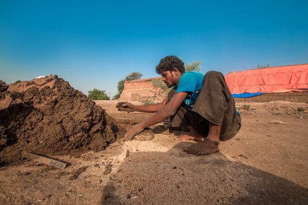 レンガ工場で手作業で伝統的なレンガを作るインドの労働者
