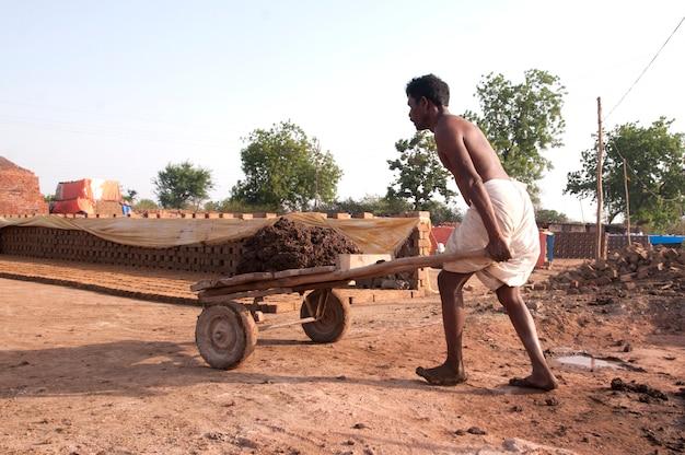レンガ工場で粘土を処理して運ぶインドの労働者
