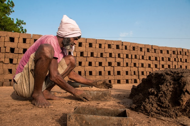 Indian workers processing on clay or mud and making in traditional bricks by hand in the brick kiln or factory or field.