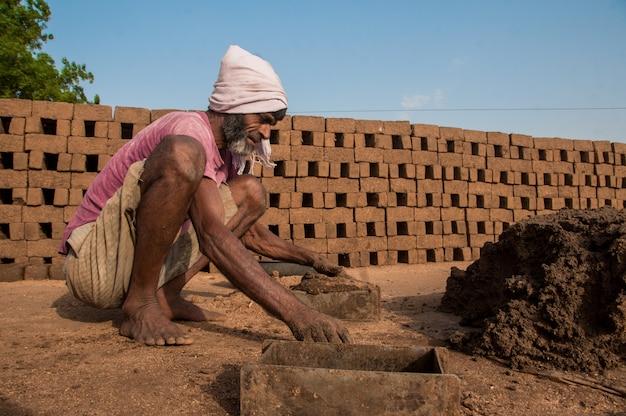 インドの労働者が粘土または泥で処理し、レンガ窯または工場またはフィールドで手作業で伝統的なレンガを作ります。