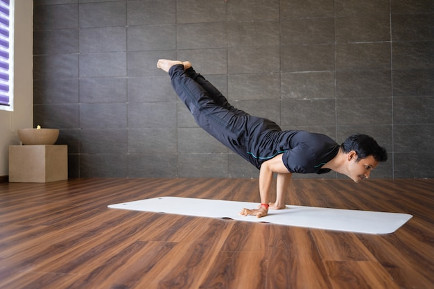 Indian yogi doing advanced hand stand yoga pose in gym
