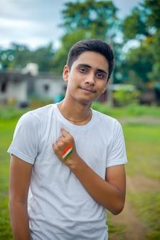 彼の手にインドの旗を持つインドの少年