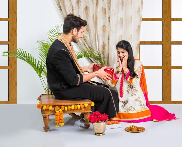Indian young brother and sister celebrating raksha bandhan or rakhi festival or on bhai dooj or bhau-beej with poja thali, sweets, gifts or taking selfie pictures