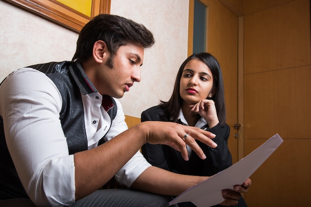 Indian young business people or lawyers consulting or discussing while holding paper or documents in hand