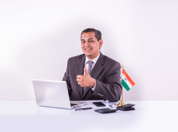 Indian young businessman or accountant with laptop calculator and indian flag