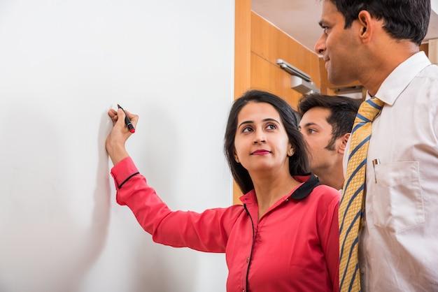 マーカーペンと探している他のビジネスマンとホワイトボードに書いているインドの若い実業家