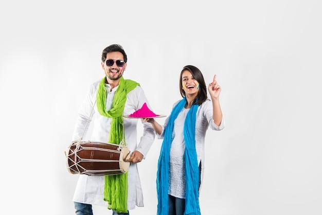 ホーリー祭を祝うインドの若いカップル。踊り、ドラムを演奏し、色でいっぱいのプレートを保持します