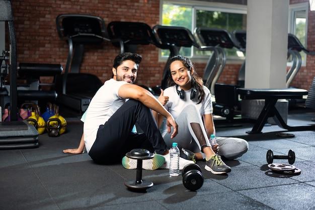 ジムで休んでいる、または運動から休憩している、水を飲んで、前向きな表現を示しているインドの若いカップル