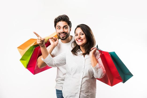 흰색 배경 위에 격리된 서 쇼핑백을 들고 가리키는 인도 젊은 부부. 선택적 초점