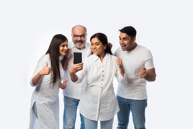 Индийская молодая пара с родителями, использующими или держащими смартфон со счастливыми выражениями, стоя на белом