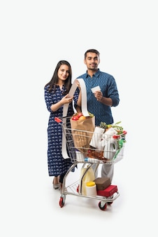 Indian young couple with shopping cart or trolly full of grocery, vegetables and fruits.  isolated full length photo over white wall