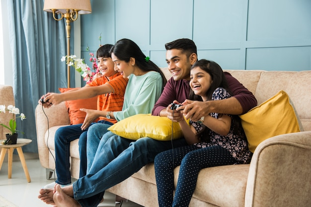Indian young family of four playing video game using controller or joystick while sitting on sofa
