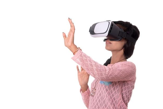 Индийская молодая девушка, смотрящая через устройство vr, очки виртуальной реальности 3d, девушка с современной технологией будущего.