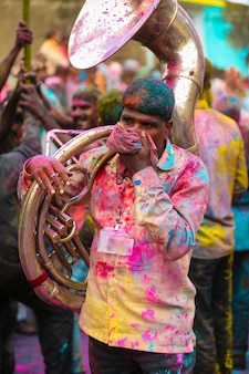 Indian young man holding tuba in holi festival free photo