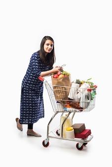 ショッピングカートまたは食料品、野菜、果物でいっぱいのトロリーを持つインドの若い女性。白い壁の上の孤立した全身写真