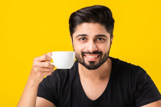 Индийский молодой человек держит чашку, пьет и наслаждается ароматным кофе. азиатский парень сидит за столом на желтом фоне с чашкой