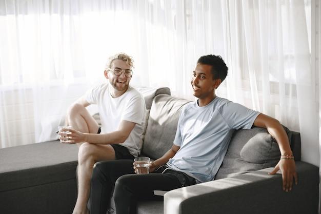 영화를 보는 인도인과 유럽인 남성. 그들은 소파에 앉아 있습니다.