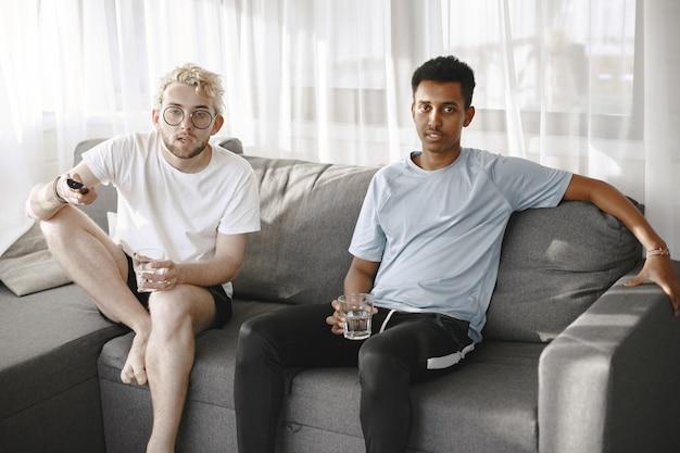 映画を見ているインディアンとヨーロッパの男性。彼らはソファに座っています。