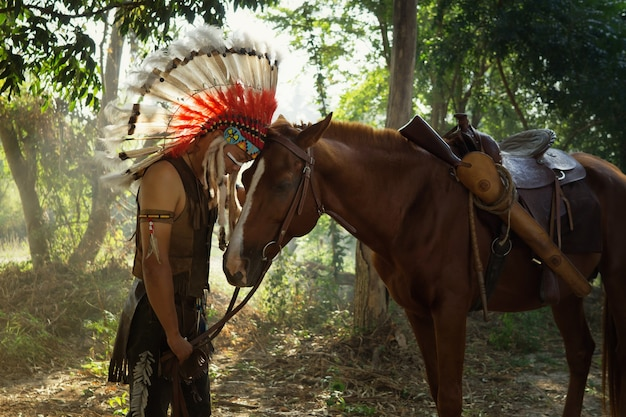 The indians are riding a horse in forest
