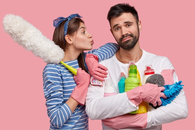 Indifferent fatigue unshaven man holds many bottles of detergent, his wife leans at shoulder, wants to kiss in cheek, holds pp duster, ready to bring house in order and clean room carefully.