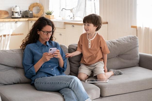 무관심한 어머니는 지루한 작은 아들이 산만해져서 짜증이 나는 소셜 미디어 서핑을 하며 엄마의 관심이 필요합니다