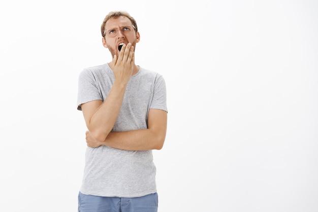 Безразличный офис-менеджер, которому скучно во время встречи с начальником, зевает, прикрывает рот ладонью и смотрит вверх, чувствуя себя беззаботным и опустошенным, не слушая неинтересную лекцию над белой стеной
