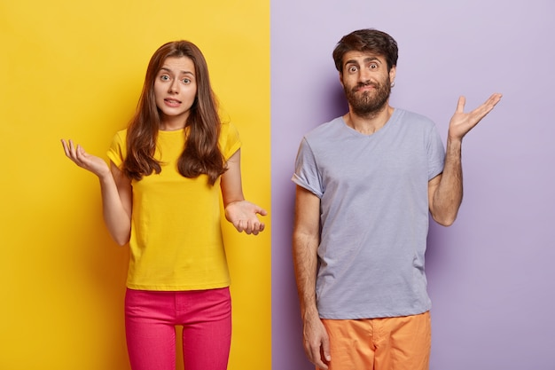 Indifferent unbothered woman and man spread hands sideways