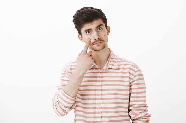 Indifferent unemotional handsome guy with beard and moustache, pointing at eyelid, having no concern about friend feelings, showing he is not crying over gray wall