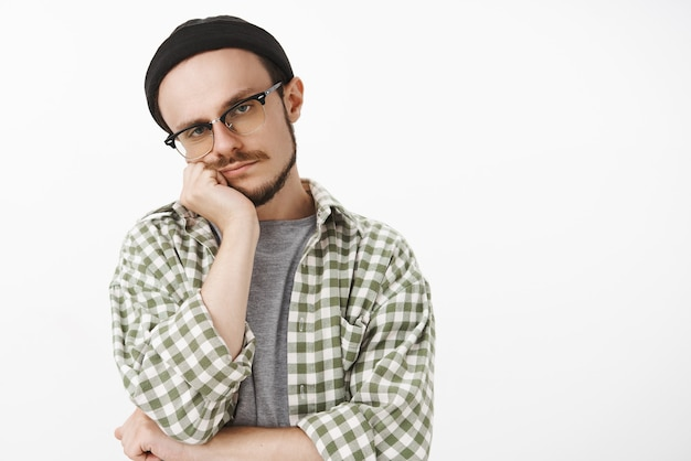 Indifferent unemotive bored good-looking man in hipster beanie glasses and checked shirt leaning head on face staring with careless and tired look feeling boredom